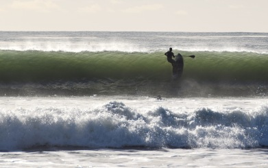 Paddle Boarder Through Wave